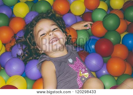 Playful Girl Lying In Ball Pit