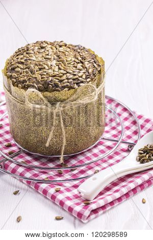 Sunflower Bread with crumbs, New Year Cloth, Teaspoons on White Table