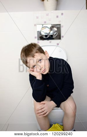 Offended Boy Sitting On The Toilet.