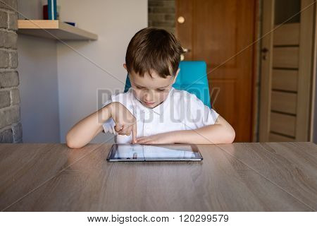 6 Year Old Boy Using Tablet While Sitting At The Table. Dressed In White Polo Shit