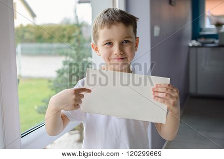 Happy Boy In A Polo Shirt, Holding An Empty Copyspace Sheet Of Paper