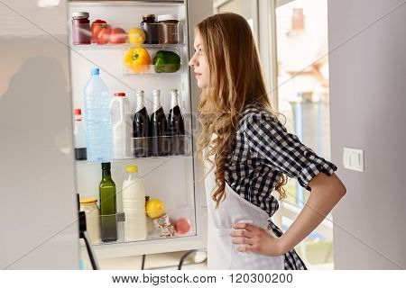 Blonde Woman Pulls Out From The Refrigerator Products
