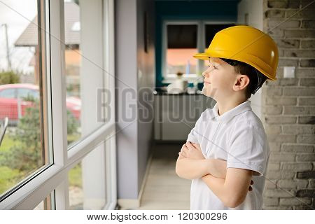 Little Boy Wearing A Engineering Helmet And Looking Throught Windows
