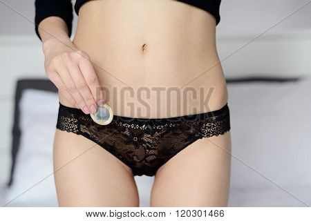 Young Sexy Woman Holding A Condom In Her Hand.