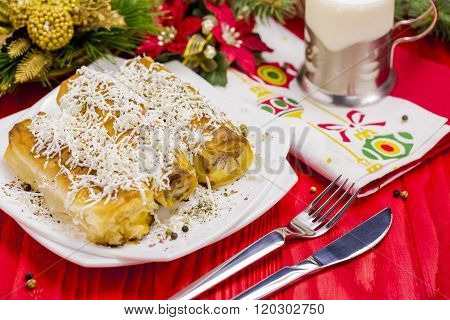 Cheese Roll Pie with Glass of Yogurt on Red Table with Christmas Tree Decoration