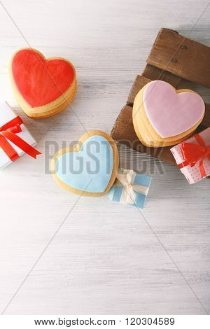 Valentine heart cookies with present boxes on wooden table, top view