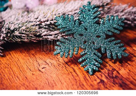 Spruce Branches In The Snow, And Blue Snowflake Wooden Background