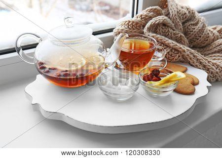 Tea set on a white wooden mat on the windowsill