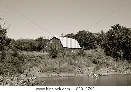 Old hip roofed barn on a river bank