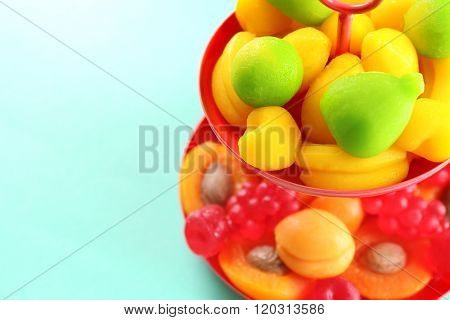 Fruit candies on stand on turquoise background