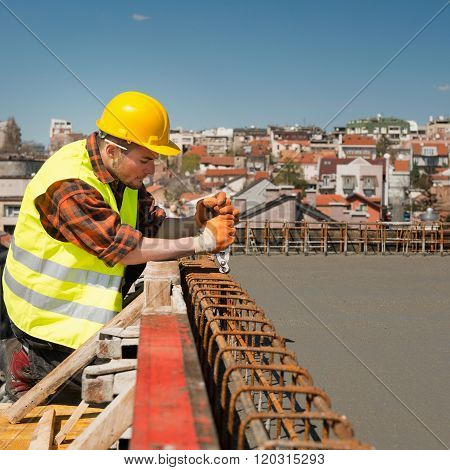 Construction Worker Tightening Wire Mesh