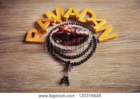 Ramadan word with wooden letters, rosary and dry dates on table
