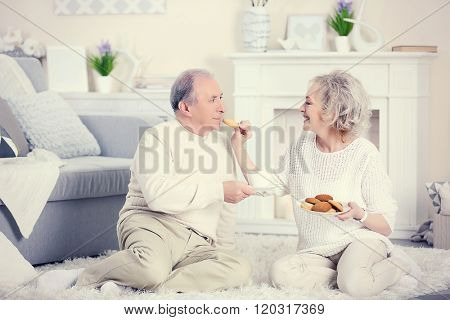Mature couple drinking tea with cookies together at home