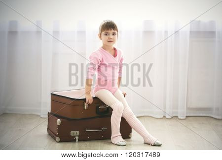 Little cute girl in pink leotard sitting on suitcases at dance studio