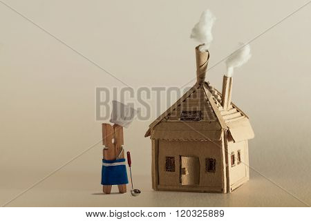 Cardboard house with chimney and white smoke. Clothespin chef character, ladle. copy space