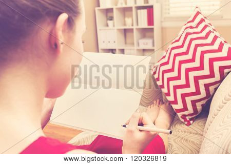 Young Woman Writing In Her Notebook On At Home