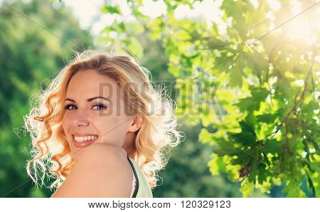 Blond woman, curly hair in green nature. Sunny summer