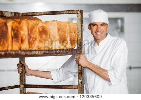 Mature Male Baker Standing By Bread Rack