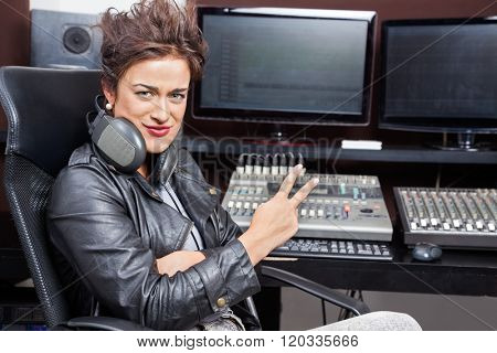 Female Professional Showing Victory Gesture At Mixing Table