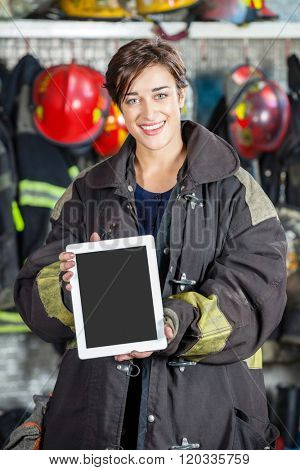 Confident Firewoman Showing Digital Tablet At Fire Station