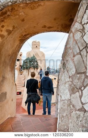 BARCELONA, SPAIN - CIRCA MAY 2015: Full Length Rear View of Couple Standing Side by Side Admiring Gaudi Sculptures on Rooftop Terrace of Casa Mila, Barcelona, Spain on Overcast Day