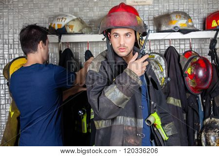 Firefighter Using Walkie Talkie With Colleague In Background