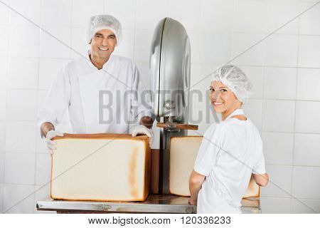 Confident Baker's Using Cutting Machine In Bakery