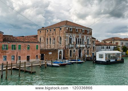 VENICE, ITALY - 17 OCTOBER 2015: Vaporetto stop on a canal on Murano Island, Venice, famous for its glass manufacturing, in front of a historic palazzo under a cloudy sky