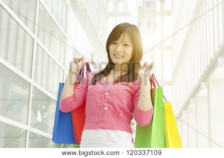 Happiness, consumerism, sale and people concept. Young Asian girl with shopping bags over mall background. Beautiful golden sunlight at back.