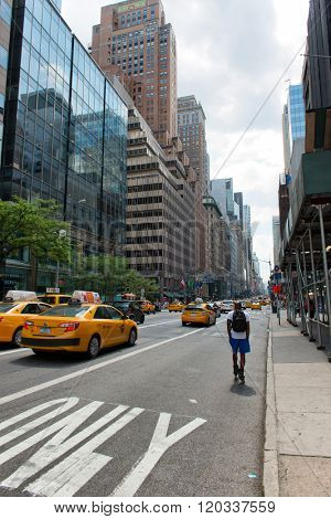NEW YORK - CIRCA SEPTEMBER 2015: Rear View of Man Rollerblading on Street Amongst Yellow Taxi Cabs on Busy City Street in New York City, New York, USA