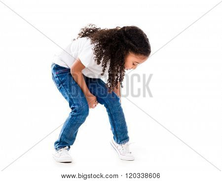 cute little girl bent down to fix shoes isolated on white background