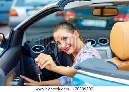 Young Pretty Woman Sitting In A Convertible Car With The Keys In Hand
