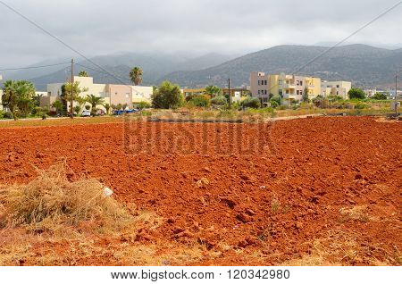View Of Red Arable Land, Malia Town And Mountain.
