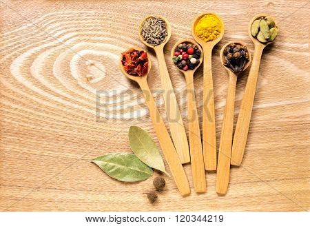 Set of several spices in wooden spoons.