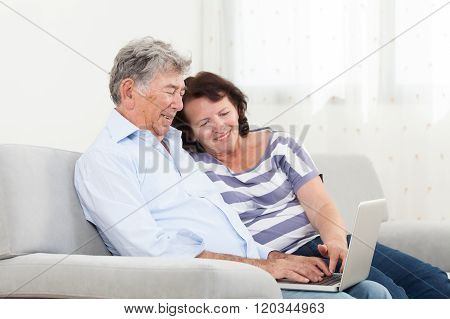 Senior couple laughing while using a laptop