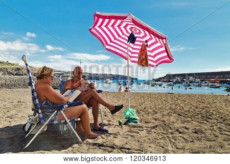 TENERIFE ISLAND, SPAIN - NOVEMBER 6, 2015 : Elderly man and woman sunbathing under the umbrella on  San Juan beach on the Tenerife island, Canary Islands
