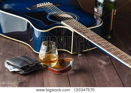 Guitar And Whiskey On A Wooden Table