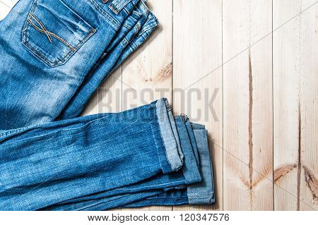 Blue Jeans On A Wooden Background.