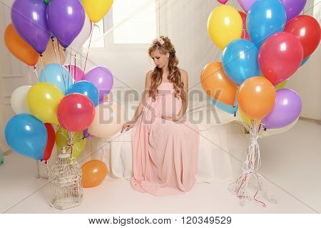 Pregnant Woman With Long Blond Hair In Elegant Dress, With A Lot Of Colorful Air Balloons