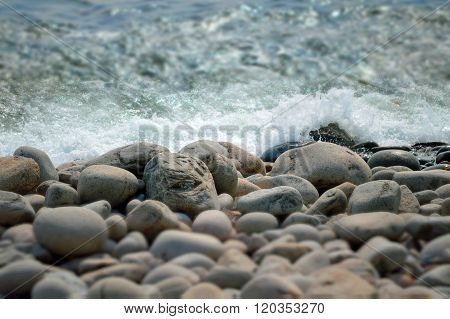 Waves crashing on the smooth stones of a beach in Maine