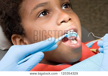 Boy having teeth examined