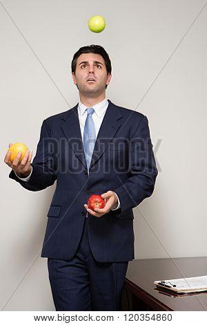 Businessman juggling fruit