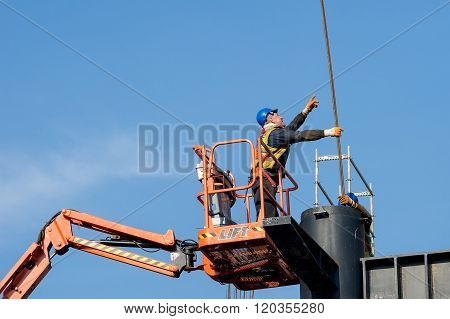 Belgrade Serbia - February 27 2016: Construction worker on a raised platform puts the reinforcement of the pillars of the building