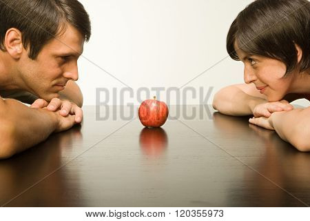 Apple on table between couple