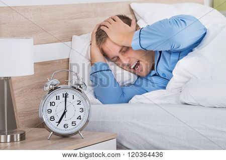 Sleeping Man Disturbed By Ringing Alarm Clock