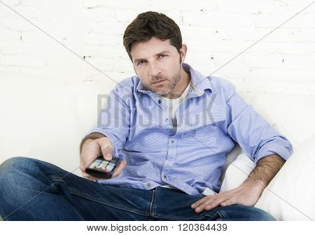 young happy man watching tv sitting at home living room sofa using remote control switching channel or volume looking intense and very interested enjoying television program or movie