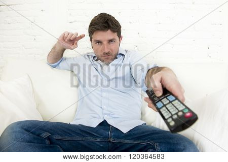 young man watching tv sitting at home living room sofa with remote control looking relaxed enjoying television program or movie