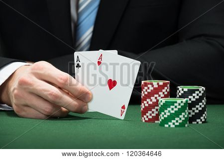 Poker Player Hand Holding Aces Of Club And Heart