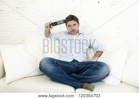 young happy man watching tv sitting at home living room sofa holding remote control looking intense and very interested enjoying television program or movie
