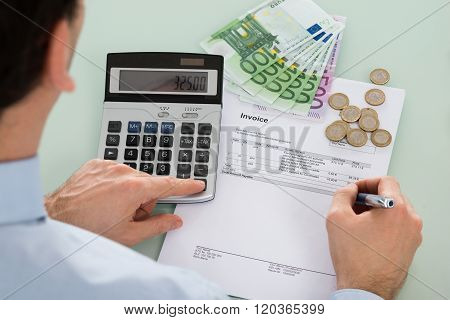 Businessman Examining Invoice With Money At Desk